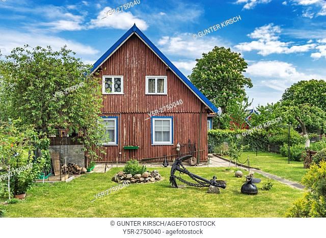 Typical House in Nida. Nida (Nidden) is a village on the Curonian Spit to the Baltic Sea. The village is located on the lagoon side of the Curonian Spit, Nidden
