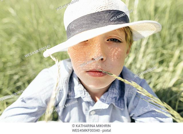 Portrait of boy wearing a hat sitting in field