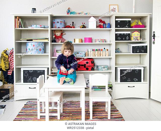 Girl playing with toys while sitting on table at home