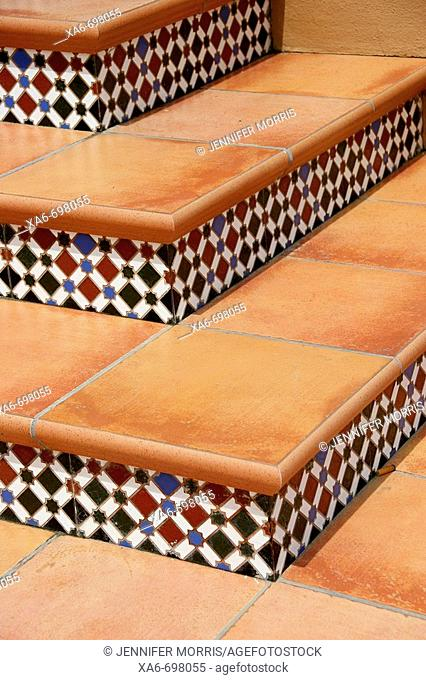 Tiles patterned in red, green, blue and white decorate the risers of the Spanish terracotta steps