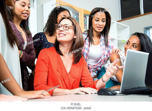 Female teacher explaining on laptop to high school students