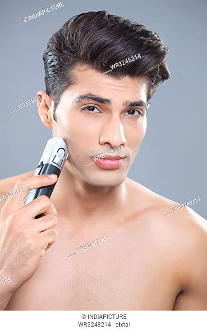 Portrait of young man using electric shaver
