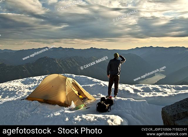 Hiker stands next to tent on mountain summit, Whistler, B.C. Canada