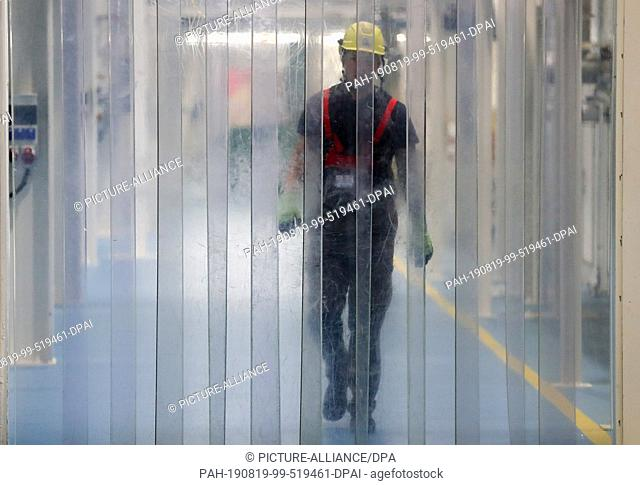 10 July 2019, Saxony-Anhalt, Leuna: An employee of a chemical company in the Leuna Chemical Park approaches a plastic strip curtain