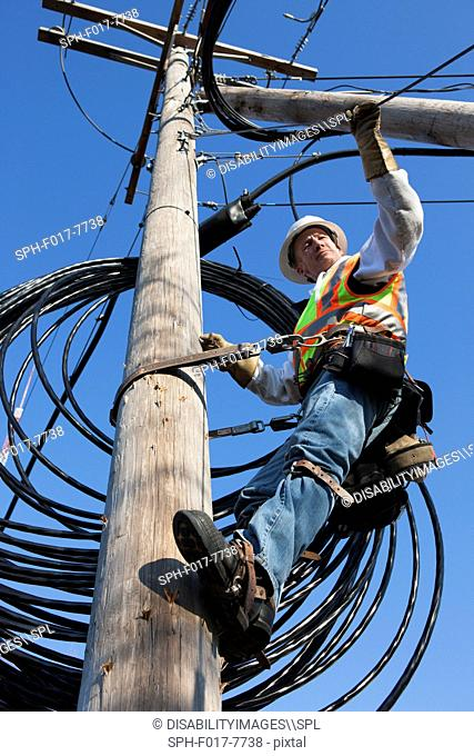 Cable lineman checking support wire tension for new cable installation