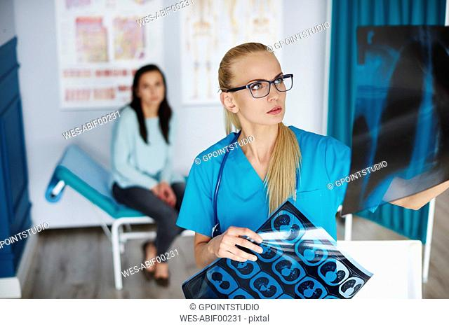 Doctor examining x-ray with woman in background