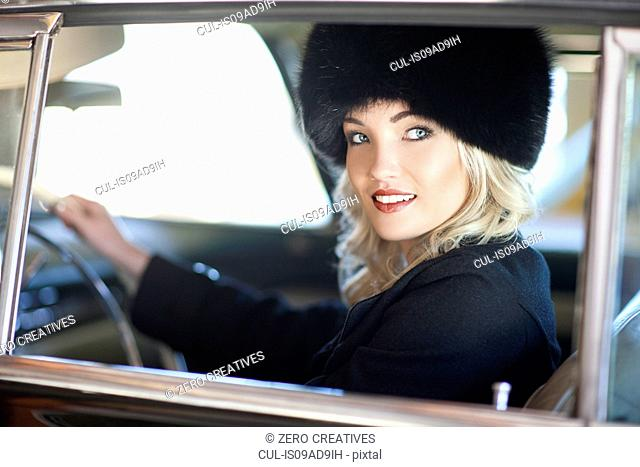Woman with fur hat driving vintage car