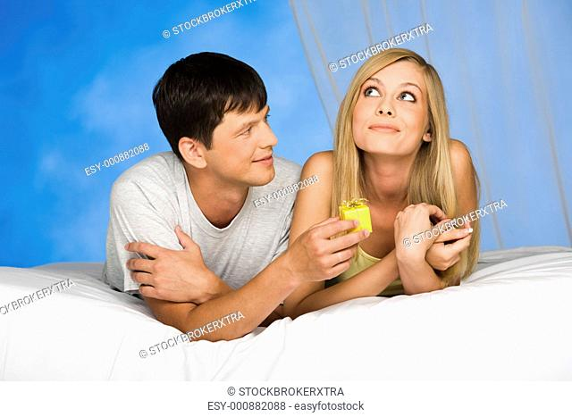 Photo of smiling man giving a present to pensive young woman