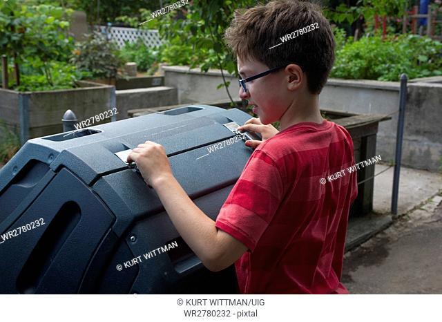 Boy Working with Compost Bins in Community Garden