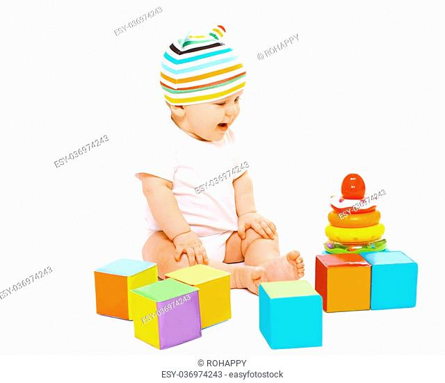 Funny baby sitting in striped hat playing with colorful toys
