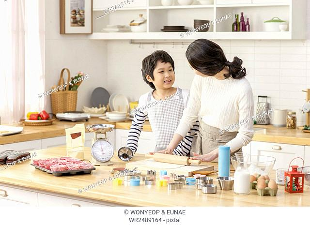 Son and mother cooking together smiling at each other