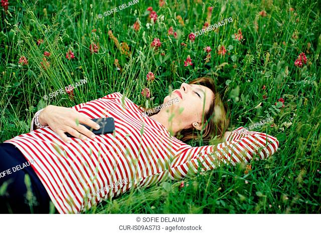 Mature woman lying on grass holding smartphone