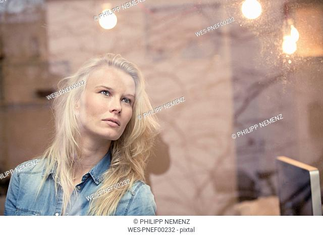 Portrait of blond woman in an office looking out of the window