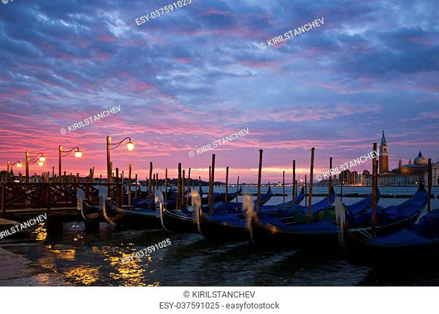 Romantic view of Venice with lampposts and gondolas near San Mark's Square with an early morning sunrise and San Giorgio Maggiore at the background