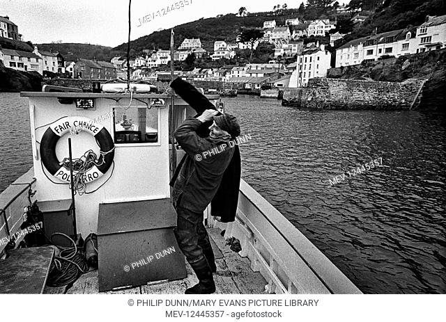 Lobster fisherman pulls on his jacket and prepares to go ashore after returning in his boat Fair Chance, to his mooring in Polperro Harbour, Cornwall, England