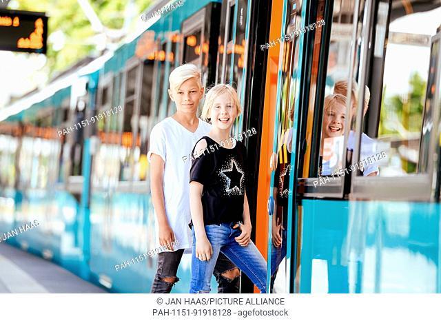 A boy and a girl get into a subway, taken on 16/07/17 in Frankfurt (model released) | usage worldwide. - Frankfurt am Main/Hessen/Germany