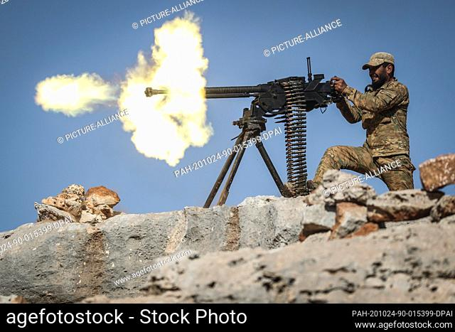 24 October 2020, Syria, Babisqa: An armed member of the National Front for Liberation (NFL) Syrian rebel coalition fires a heavy machine gun during a military...