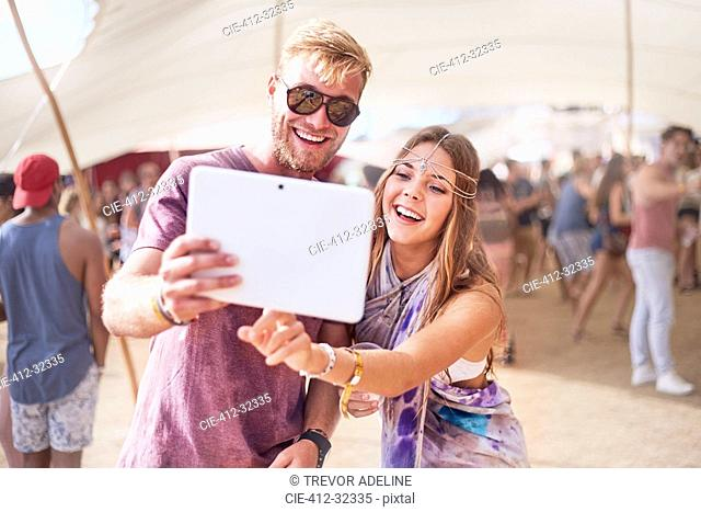 Young couple taking selfie with digital tablet at music festival