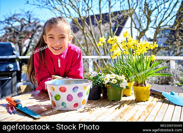 portrait of happy girl planting flowers on balcony