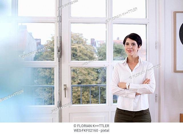 Portrait of confident woman standing at the window
