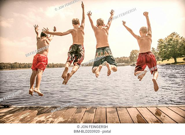 Caucasian boys jumping off wooden dock