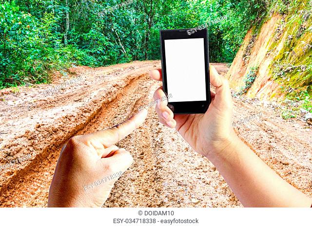 Business conceptual- Focused on right hand holding empty mobile with Trekking dirt road