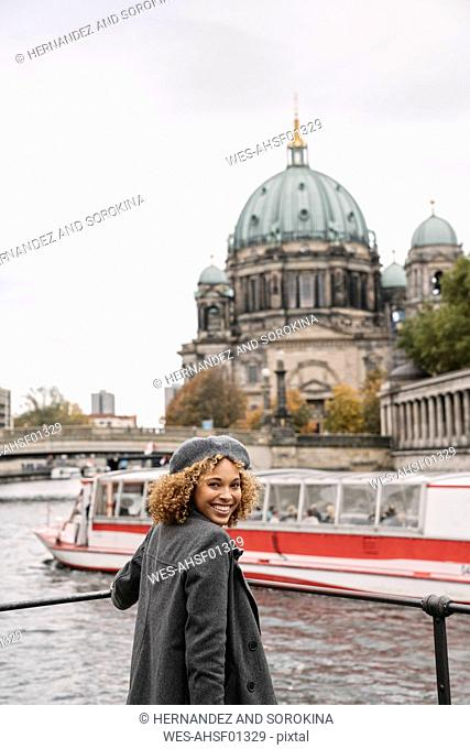 Happy tourist woman in the city at Spree river, Berlin, Germany