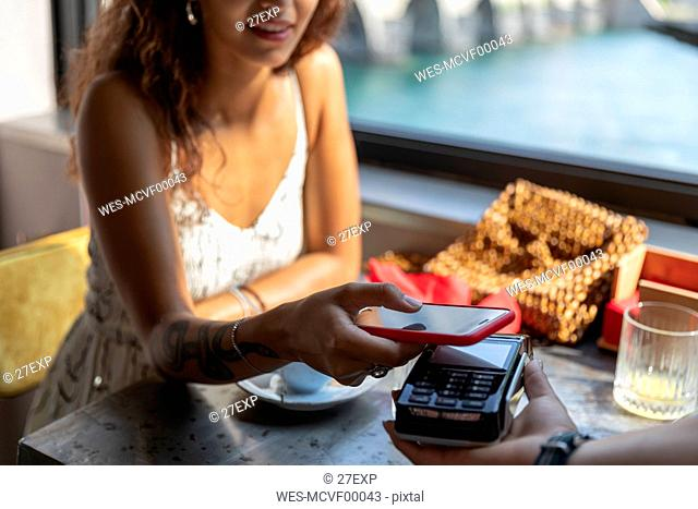 Young woman paying bill with smartphone at coffee shop