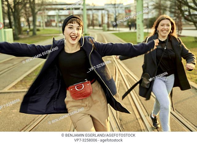 two adventurous women running at street in city Cottbus, Brandenburg, Germany