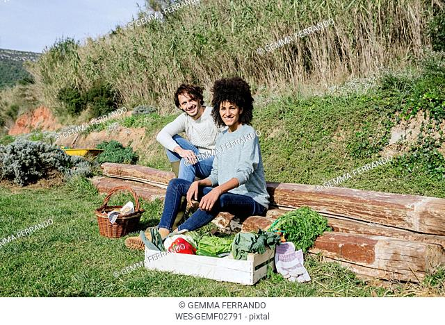 Couple sitting in their vegetable garden, having a picnic after harvesting