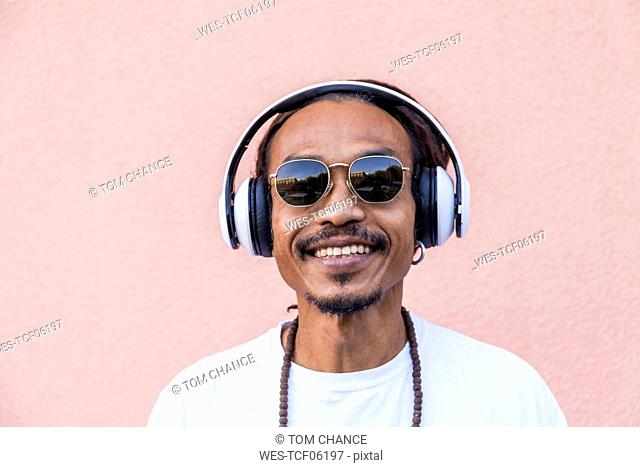 Portrait of mature man with dreadlocks and headphones, listening music