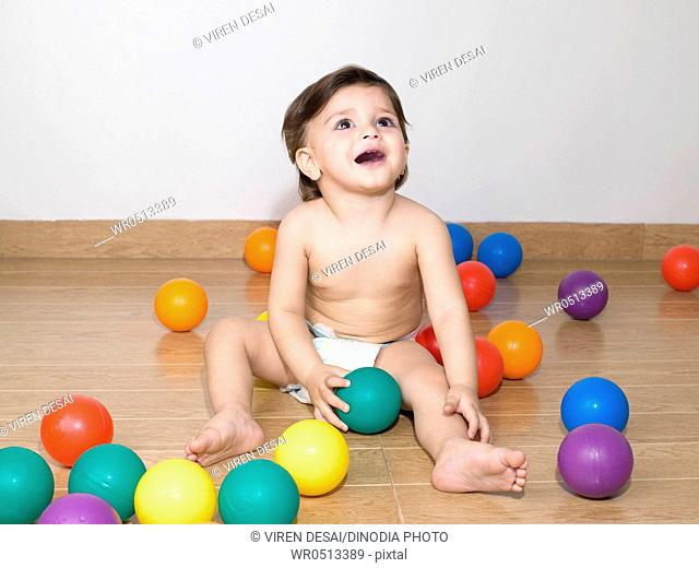 Baby playing with colourful balls , MR779N