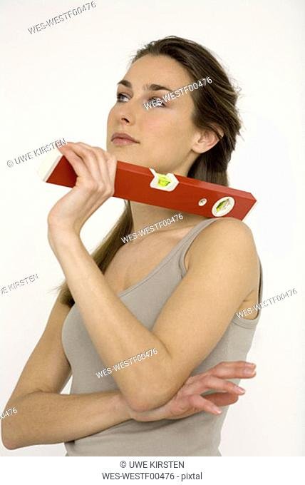 Young woman holding red spirit level, close-up