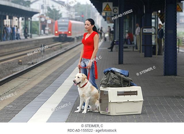 Woman with Labrador Retriever on leash baggage and kennel on platform railway station luggage