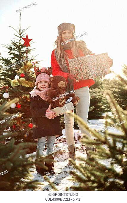 Girl and mother in christmas tree forest with christmas presents, portrait