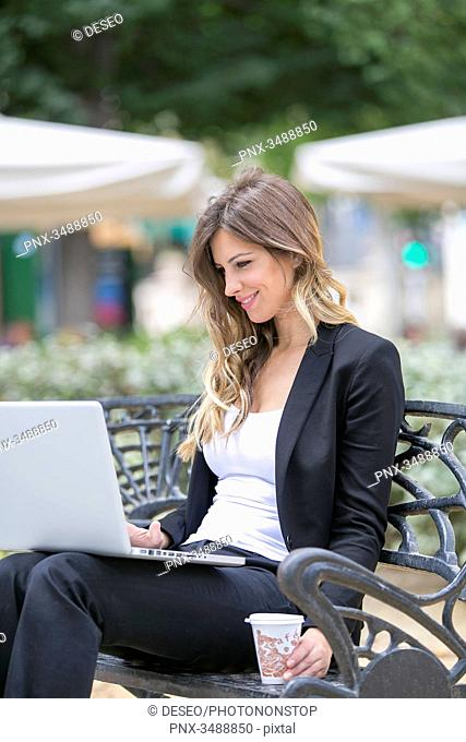 Executive woman with laptop sitting in a bank