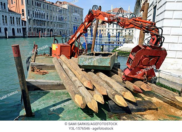 Wooden stakes and machinery by canal, Venice, Italy