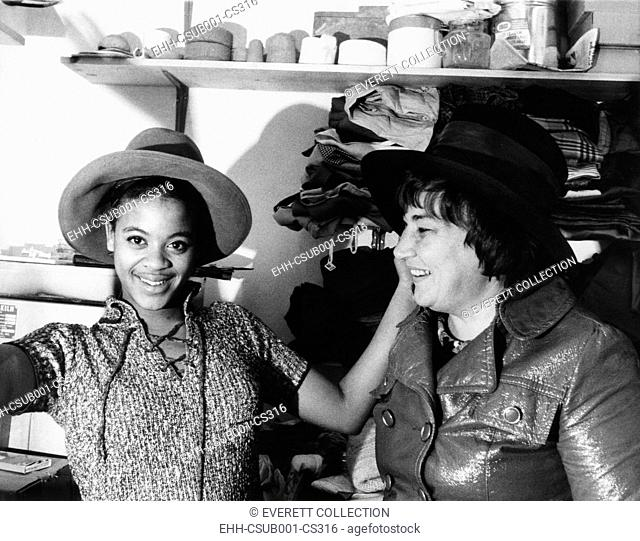 A high school student tries on one of Bella Abzug's wide brimmed campaign hats. Congresswomen-elect Abzug donated the hat to the boutique, 'Square Business'