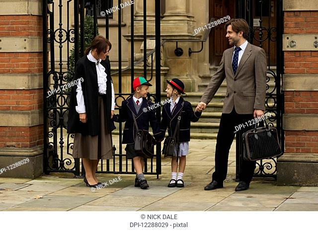 Family of four at an old school gate; London, England