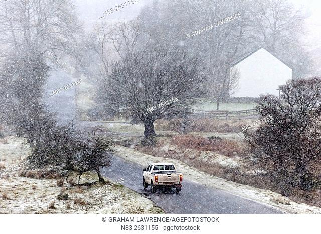 A four wheel drive vehicle negotiates a small road, during a blizzard, between Upper Chapel and Garth, Powys, Wales, UK