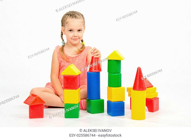 Four-year girl playing in a European-style cubes, isolated on a light background