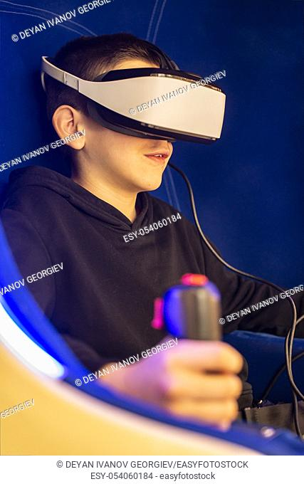 Child playing game with VR glasses. Blue illuminated cabin with joysticks. Special effects. Technology, entertainment and gaming concept with virtual reality...