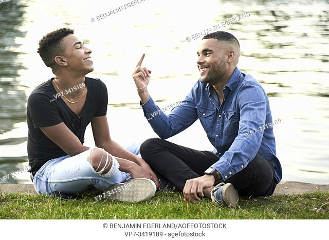 Gay couple sitting on the grass. Frankfrut am Main, Germany