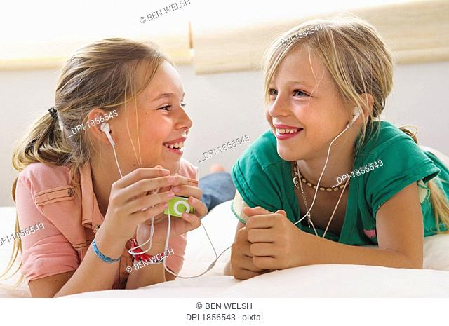 Two girls listening to music player