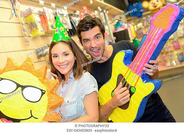 Couple in joke shop with fun props