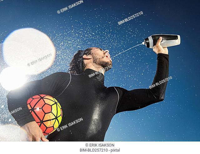 Hispanic man holding soccer ball spraying water into mouth