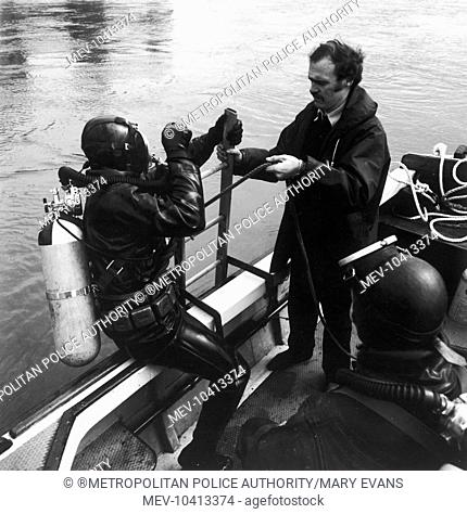 A diver of the Underwater Search Unit of the Metropolitan Police boarding a Thames Division launch after searching in the River Thames, London