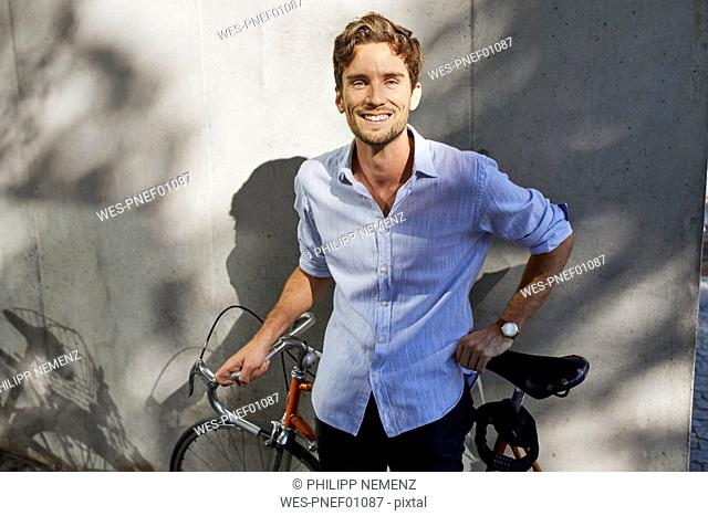 Portrait of smiling young man with racing cycle in front of concrete wall