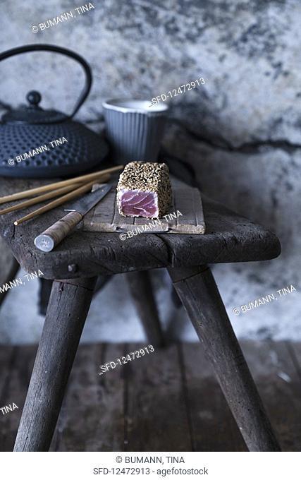 Unsliced tuna fish tataki on a rustic wooden stool (Japan)