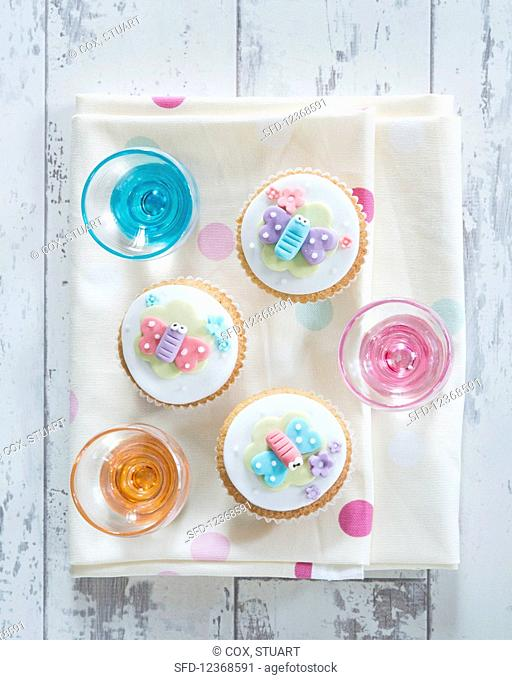 Cupcakes decorated with decorative butterflies and blossoms (supervision)